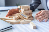 Cropped view of lawyer holding hands near blocks wood game construction with copyright lettering collapsing on blurred background