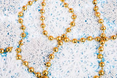 Close up view of golden beads with decorative snowflakes and artificial snow on blue background, new year concept stock vector