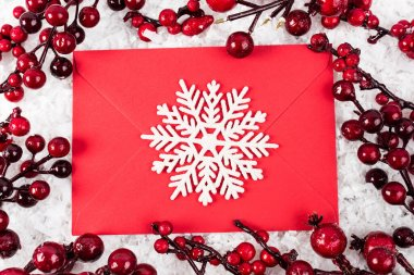 Top view of decorative snowflake on red envelope near branches with artificial berries on white textured background, new year concept stock vector