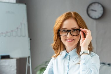 Happy redhead businesswoman touching frame of eyeglasses, while looking at camera in office on blurred background stock vector
