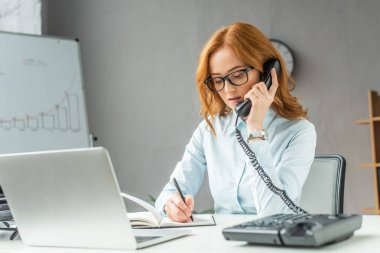 Redhead businesswoman talking on landline telephone, while writing in notebook at workplace on blurred foreground stock vector