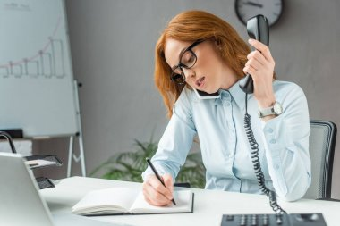 Redhead businesswoman with handset talking on mobile phone, while writing in notebook at workplace on blurred background stock vector