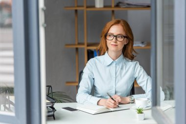 Positive businesswoman writing in notebook, while looking away at workplace with blurred window on foreground stock vector