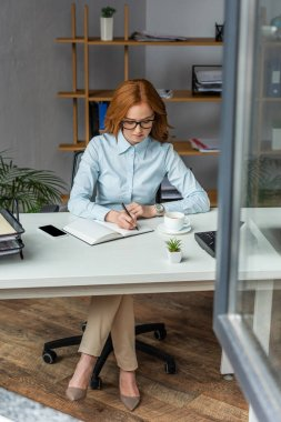 Full length of businesswoman writing in notebook , while sitting at workplace with blurred window on foreground stock vector