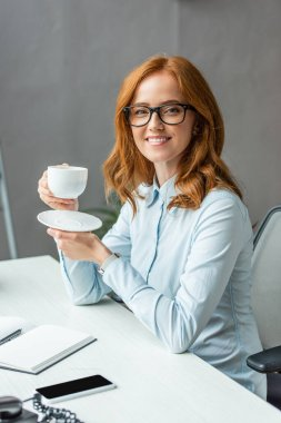 Happy businesswoman with coffee cup and saucer looking at camera, while sitting at table on blurred background stock vector