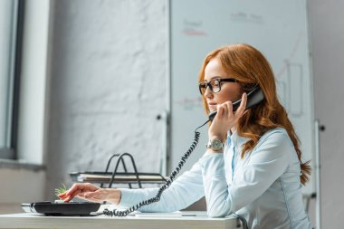 Focused businesswoman with handset dialing number on landline telephone, while sitting at workplace on blurred background stock vector