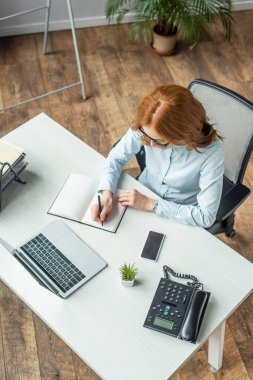 Genel görünüm kızıl saçlı iş kadını, iş yerinde cihazlarla otururken deftere yazı yazıyor.