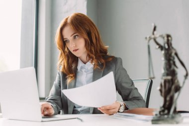 Redhead female lawyer with paper sheet looking at laptop at workplace with blurred themis figurine on foreground stock vector