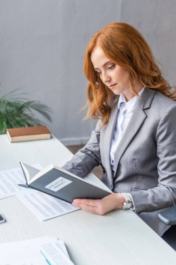 Redhead lawyer reading book with intellectual property lettering at workplace with documents on blurred background stock vector