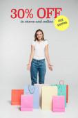 mladá radostná žena stojící a ukazující rukama na nákupní tašky v blízkosti zdarma lodní nápisy na šedé