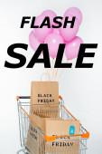 nákupní tašky s černým pátek v košíku s růžovými balónky v blízkosti bleskového prodeje nápisy na bílém