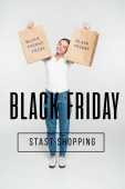 pleased woman with closed eyes holding shopping bags near black friday stast shopping lettering on white