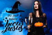Photo woman in black dress and veil holding pumpkin and burning candles near it is just bunch of hocus pocus lettering on blue with smoke