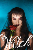 Photo evil woman with black makeup and dark veil holding rose near witch lettering on blue