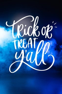 Trick or treat yall lettering on dark blue background with smoke stock vector
