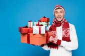 Glücklicher Mann mit Strickhandschuhen und Hut, der ein Bündel von Geschenkboxen in blauer Isolation hält