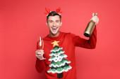 Vidám férfi karácsonyi pulóverben és fejpánt tartó üveg és üveg pezsgő piros alapon