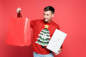 Smiling man in sweater with christmas tree holding shopping bags and gift box on red background