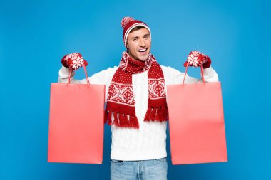 Happy young adult man in mittens holding red paper bags isolated on blue stock vector