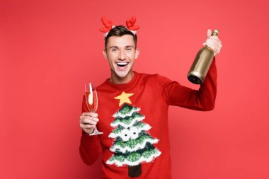 Cheerful man in christmas sweater and headband holding bottle and glass of champagne on red background stock vector