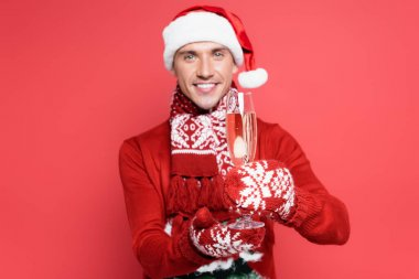 Glass of champagne in hands of man in santa hat and mittens on red and blurred background stock vector