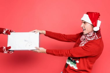 Excited man in santa hat and scarf pulling gift box on red background stock vector