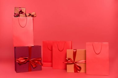 Gift boxes with bows and shopping bags on red background stock vector