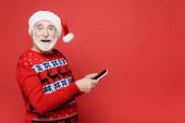Lächelnder älterer Mann mit Weihnachtsmütze und rotem Smartphone