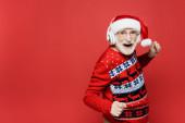 Veselý senior muž v Santa klobouku a sluchátka tanec izolované na červené