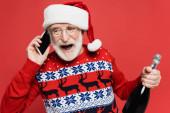 Fröhlicher Senior mit Weihnachtsmütze spricht auf Smartphone, während er eine Flasche Champagner auf Rot hält