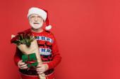 Lächelnder älterer Herr mit Weihnachtsmütze, Geschenk und Rosenstrauß auf rotem Grund
