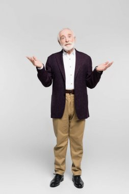 Confused senior man in jacket and shirt showing shrug gesture on grey background stock vector
