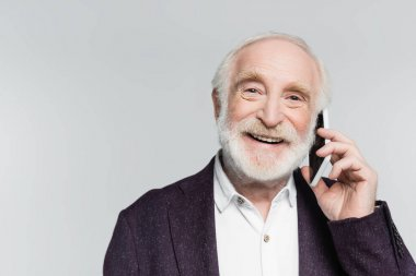 Smiling elderly man talking on smartphone isolated on grey stock vector