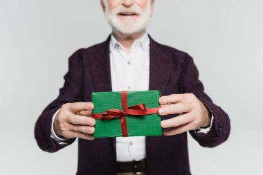 Cropped view of gift box in hands of smiling senior man on blurred background isolated on grey stock vector
