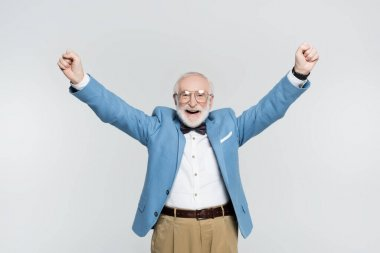 Cheerful senior man showing yeah gesture isolated on grey stock vector