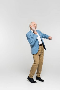 Cheerful senior man in blue jacket and bow tie dancing on grey background