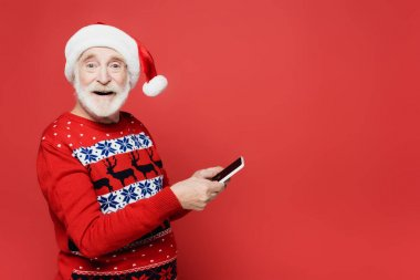 Smiling elderly man in santa hat holding smartphone isolated on red stock vector