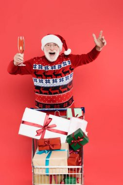 Excited man in santa hat holding glass of champagne near shopping cart with gifts isolated on red stock vector
