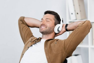 Smiling businessman in headphones relaxing while listening to music on blurred background stock vector
