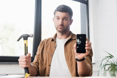 Sad businessman with hammer looking at camera while showing damaged smartphone with blurred window on background stock vector