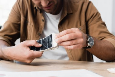 Cropped view of businessman disassemble smashed smartphone while sitting at table on blurred foreground stock vector