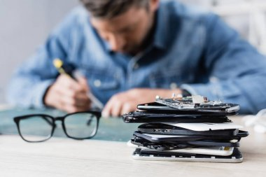 Close up view of pile of broken mobile phones near eyeglasses on workplace with blurred repairman on background stock vector