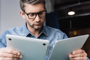Focused repairman in eyeglasses looking at damaged laptop on blurred foreground stock vector