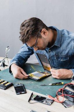 Repairman in eyeglasses looking at disassembled broken digital tablet near screwdriver and multimeter at workplace stock vector