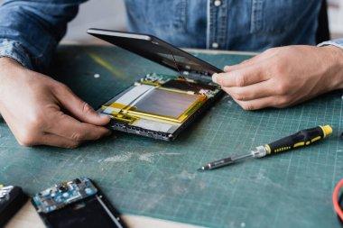Close up view of repairman hands disassembling broken digital tablet near screwdriver at workplace stock vector
