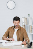 Focused businessman looking at paper sheet while counting on calculator at workplace on blurred background