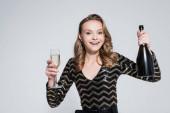 fröhliche Frau hält Glas Champagner und Flasche isoliert auf grau
