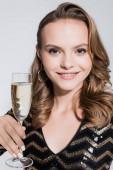 usmívající se mladá žena drží sklenici šampaňského izolované na šedi