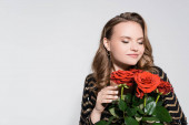 happy young woman smelling bouquet of red roses isolated on grey