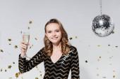 vidám fiatal nő kezében pohár pezsgő közelében disco labda és esik konfetti szürke